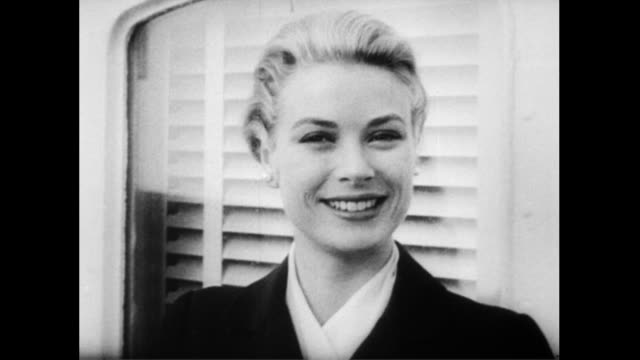 / ship pulls into harbor at monaco / grace kelly on board smiling / monaco civilians sitting on rocks in the harbor to greet grace kelly as she... - grace kelly actress stock videos and b-roll footage