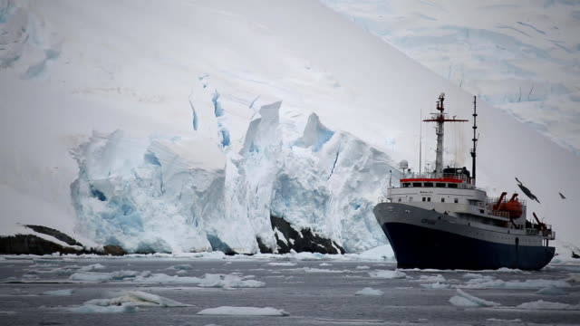 ship sailing in antarctic waters on background of glacial mountain - antarktis stock-videos und b-roll-filmmaterial