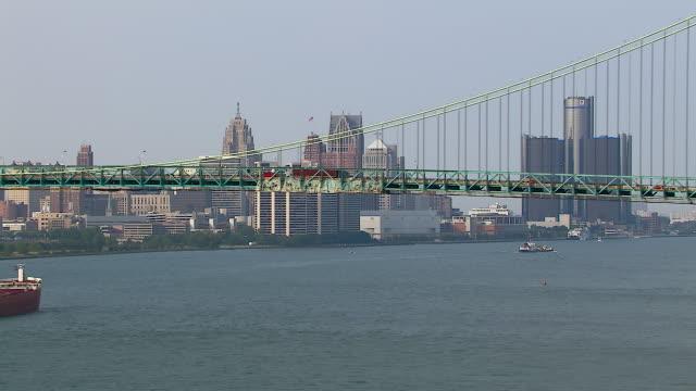 ship sails detroit river under bridge - detroit river stock-videos und b-roll-filmmaterial