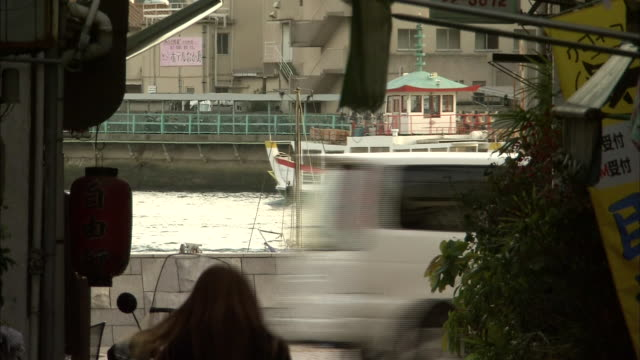 a ship sails past an alley in an onomichi retail district. - onomichi hiroshima stock videos and b-roll footage