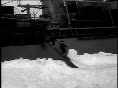 ship stopped in a glacier / sailors walking off a ship onto the ice / ship breaking through the ice / group of explorers hiking on the snow and ice /... - 1954 stock videos & royalty-free footage