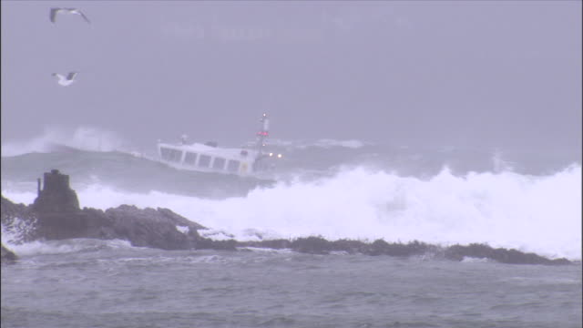 a ship, the pilotos, negotiates storm waves along a rocky coastline. - ship stock videos & royalty-free footage