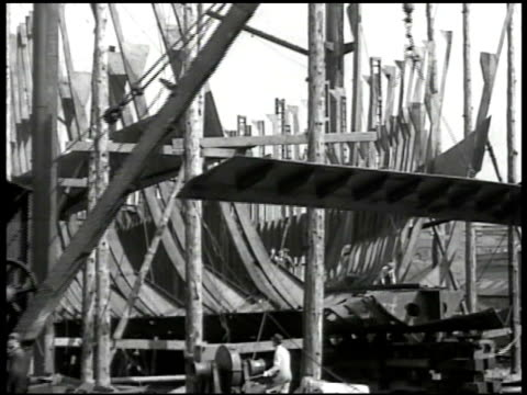 ship yard ships in harbor ws crane w/ large metal piece men working on giant ship frame bg ms man w/ large spot welder ms woman w/ fork tossing... - warship stock videos & royalty-free footage
