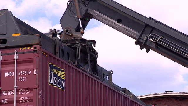 vidéos et rushes de shipping container being picked up and carried by a vehicle at antwerp port - carrying