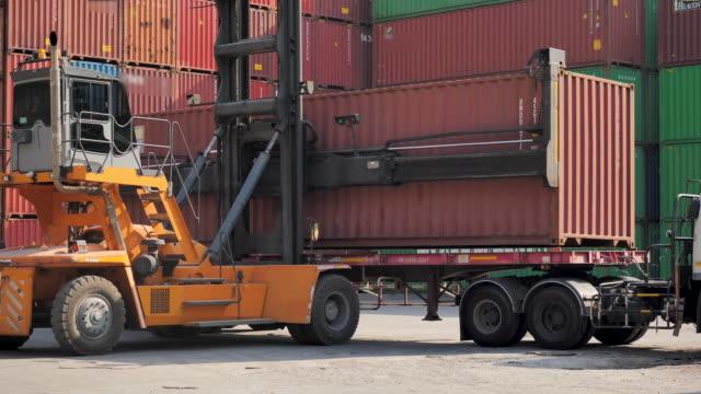 vidéos et rushes de boîte de transport de camion de chargeur de récipient d'expédition. - décharger