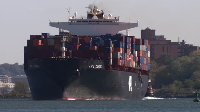A shipping container ship is pushed by a tug boat into harbor