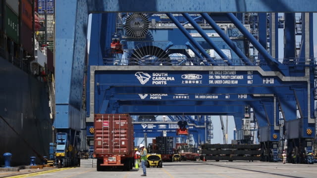 Shipping containers are transported at the Port of Charleston Wando Welch Terminal in Charleston South Carolina US on Wednesday May 9 2018