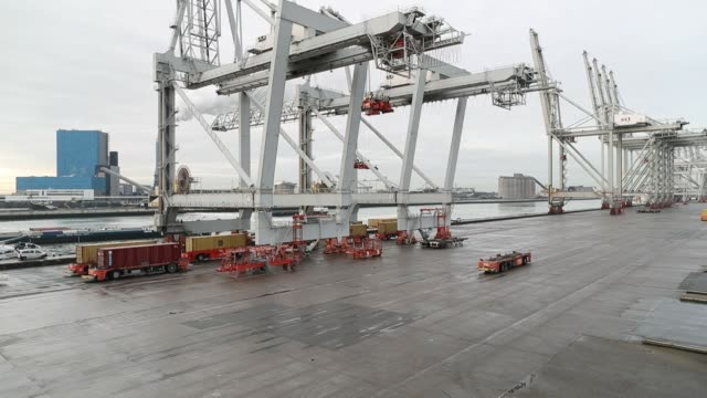 shipping containers are transported by automated guided vehicles beside gantry cranes on the dockside at the delta terminal, operated by europe... - crane stock videos & royalty-free footage