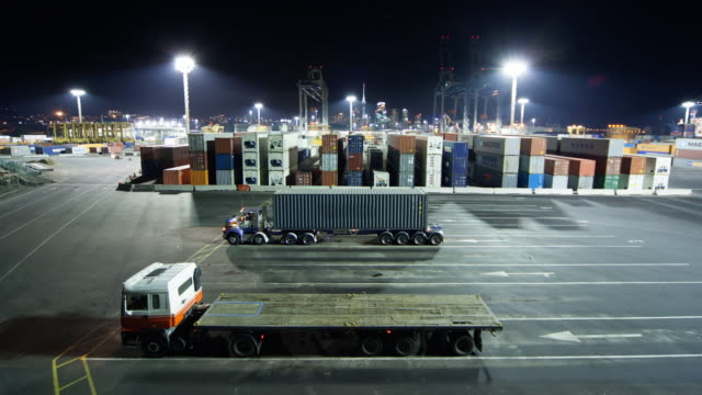 tl ha ws shipping containers being loaded onto semi trucks at ports of auckland at night/ auckland, new zealand  - straddle carrier stock videos & royalty-free footage
