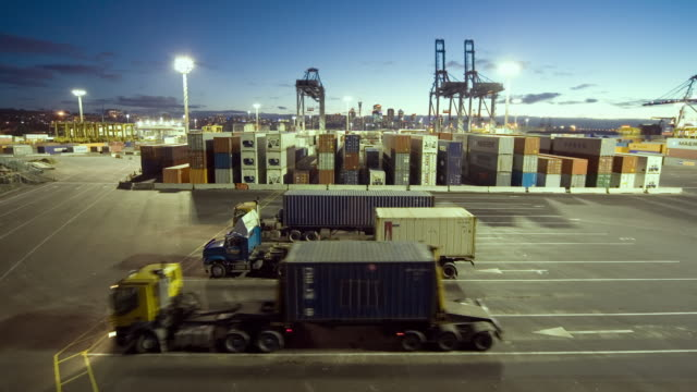 tl ha ws shipping containers being loaded onto semi trucks at ports of auckland from dusk to night/ auckland, new zealand  - straddle carrier stock videos & royalty-free footage