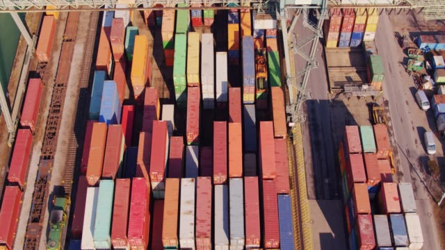 shipping containers beneath straddle carrier - drone shot with upwards tilt - straddle carrier stock videos & royalty-free footage