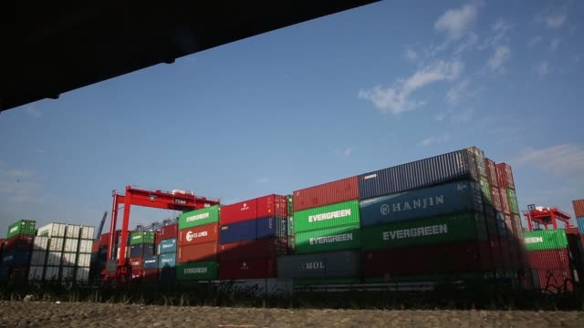 Shipping containers sit stacked at the Kwai Tsing Container Terminals in Hong Kong China on Monday Nov 24 A gantry crane moves a China Ocean Shipping...