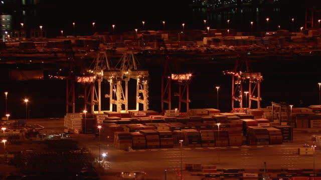 Shipping containers stacked at the container terminal at Port of Long Beach in California at night.