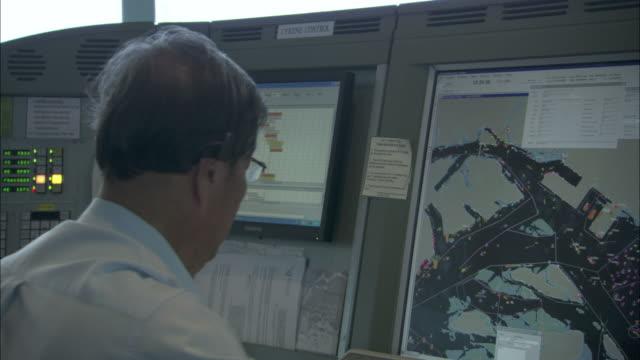 A shipping lane controller monitors ship traffic on a screen.