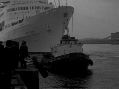 liner canberra arrives at southampton england hampshire southampton liner coming into dock gv ditto tugs pull her in fv tug pulls her ms bow of ship... - イングランド サウサンプトン点の映像素材/bロール