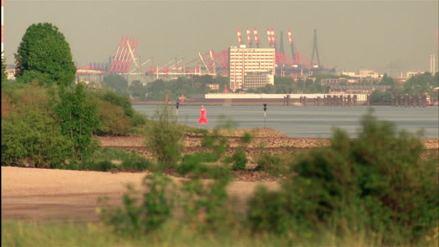 time lapse long shot ships and boats pass by on elbe river with cranes at port in background from day to dusk / hamburg, germany - day to dusk stock videos & royalty-free footage