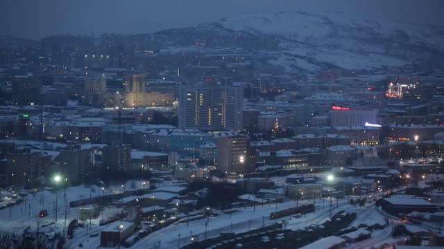 Ships and rail freight wagons sit illuminated by sodium lights at the port of Murmansk on the eastern shore of Kola Bay in Murmansk Russia on Friday...
