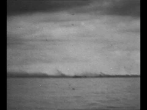 ws ships at sea near palau with flashes from ship guns in background pan to smoke rising from explosions on shore during world war ii battle for... - amphibious vehicle stock videos & royalty-free footage