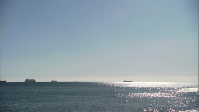 Ships cruise on the glittering Mediterranean Sea off Gibraltar. Available in HD.