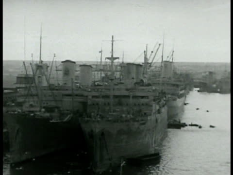 ships docked in unidentified north african port. us soldiers walking on dock w/ transport ships docked bg. world war ii wwii. anglo-american invasion... - 1942年点の映像素材/bロール