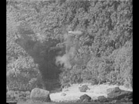 us ships fire guns rockets during initial assault on okinawa during world war ii / rockets hit cave entrance on shore / battleship fires as landing... - landing craft stock videos & royalty-free footage
