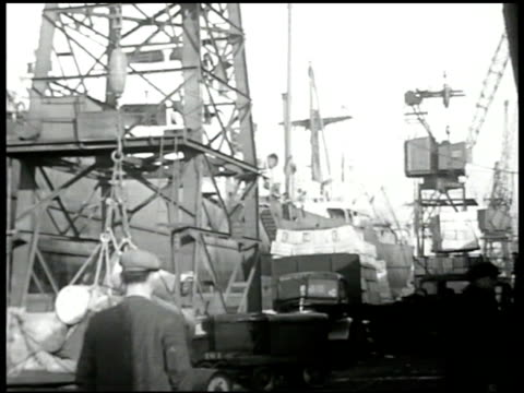 vidéos et rushes de ships in harbor ws ship crane unloading cargo ms us flag on ship vs grain pouring out of chute into hold grain bags vs english dock workers loading... - débardeur
