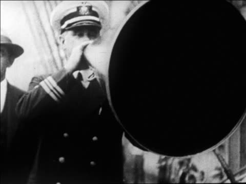 ship's officer yelling into megaphone before byrd's expedition to north pole / newsreel - 1926年点の映像素材/bロール