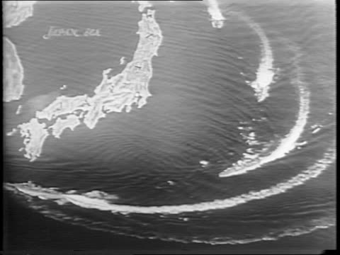 ships on horizon of ocean with clouded sky / aerial view of two battleships / rounds are fired from deck guns / explosions onshore / more rounds are... - water fight stock videos & royalty-free footage