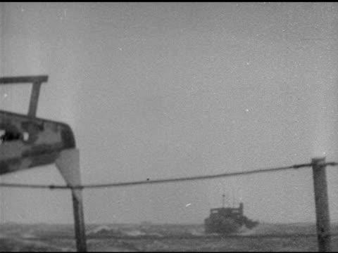 vidéos et rushes de ships on rough sea, bad weather. us soldiers climbing down ship to landing craft. landing craft leaving ship's side. silhouette of large landing... - cuirassé