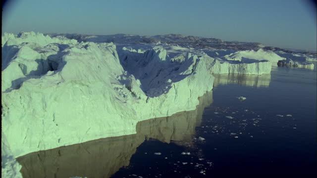 vidéos et rushes de aerial ships sailing around an iceberg at dusk - iceberg bloc de glace