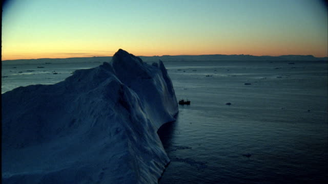 vidéos et rushes de aerial ships sailing between large icebergs. - vignetage