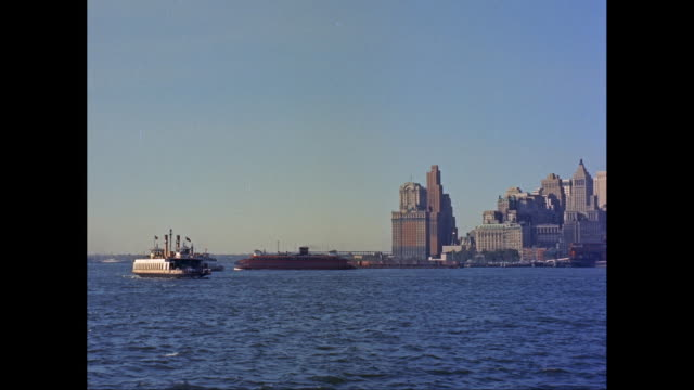 ws pan  ships, staten island ferry moving in new york harbor, skyline in background / new york city, new york state, united states - porto di new york video stock e b–roll