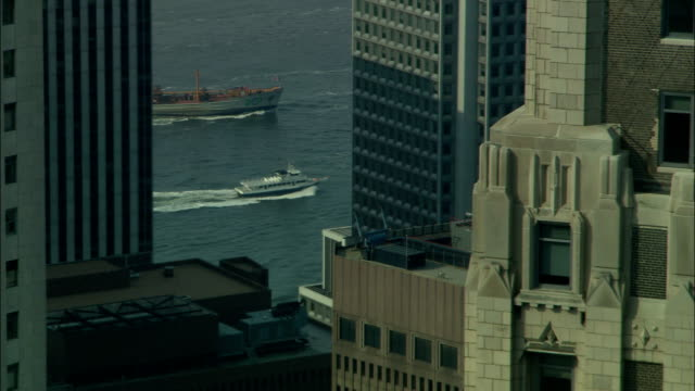ships travel across a bay behind manhattan skyscrapers. - manhattan video stock e b–roll