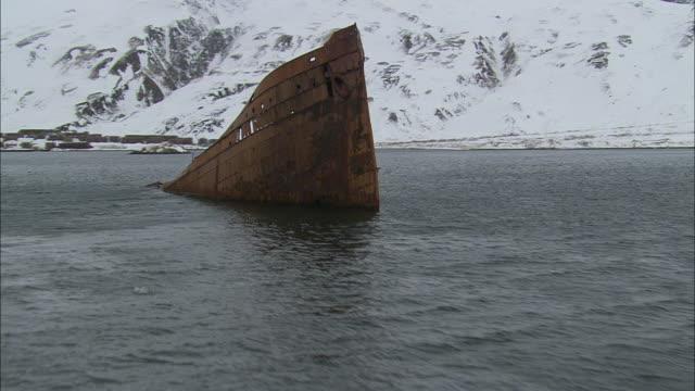 stockvideo's en b-roll-footage met a shipwreck protrudes from alaska's dutch harbor. - scheepswrak