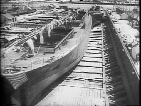 vídeos de stock e filmes b-roll de a shipyard launching area / a cargo ship in the launching area decorated with flags / two cargo ships in a shipyard / shipyard workers turning... - construtor de navios