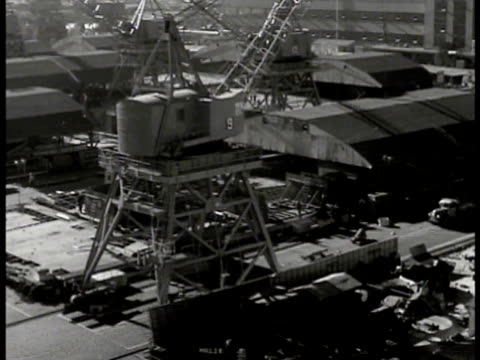 shipyard w/ mechanized cranes moving on docks over workers men workers welders welding tu bow of warship under construction crane scaffolding fg... - 造船所の労働者点の映像素材/bロール