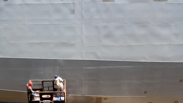 Shipyard worker paint the ship