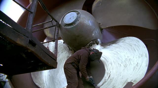 ms tu td shipyard worker polishing ship's propeller in dry dock, reykjavik, iceland - costruttore navale video stock e b–roll