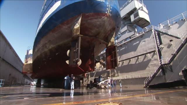 shipyard workers inspect the hull of a ship in dry dock. - qualitätsprüfer stock-videos und b-roll-filmmaterial