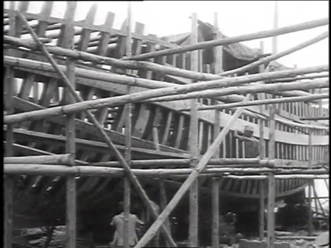 shipyard workers using tools on a ship's deck / shipwright working on wooden boat / worker chopping wood on an unfinished boat - timber stock videos & royalty-free footage