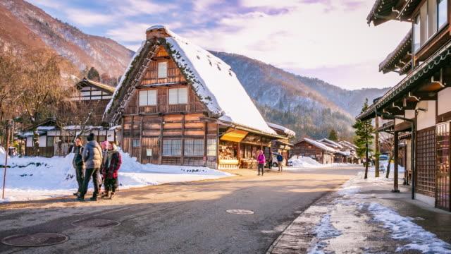 shirakawago dorf sonnenuntergang mit weißen schnee und publikum mit menschen-touristen, die reisen in japan-zeitraffer - unesco welterbestätte stock-videos und b-roll-filmmaterial