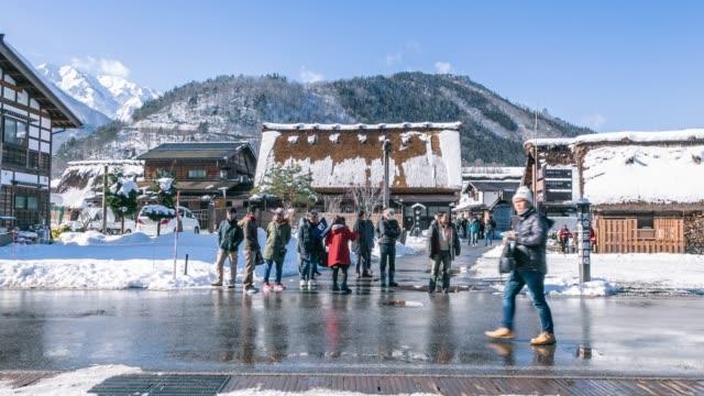 vídeos de stock e filmes b-roll de shirakawago village with white snow and crowd with people tourist travelling in japan timelapse - telhado de palha
