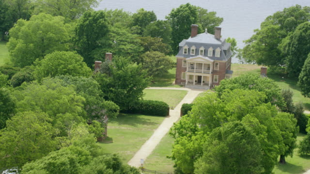 WS AERIAL POV Shirley Plantation surrounded by trees, James River in background / Charles City, Virginia, United States
