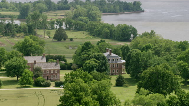 ws aerial pov shirley plantation surrounded by trees, james river in background / charles city, virginia, united states - 植民地様式点の映像素材/bロール