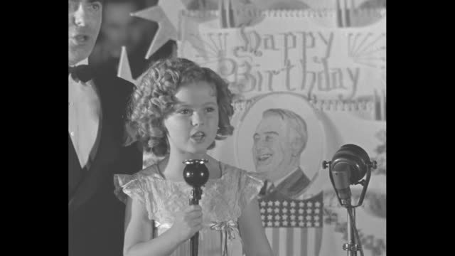vídeos de stock e filmes b-roll de vs shirley temple and eddie cantor at celebration for president franklin d roosevelt's birthday shirley sings and eddie conducts auction for a piece... - shirley temple