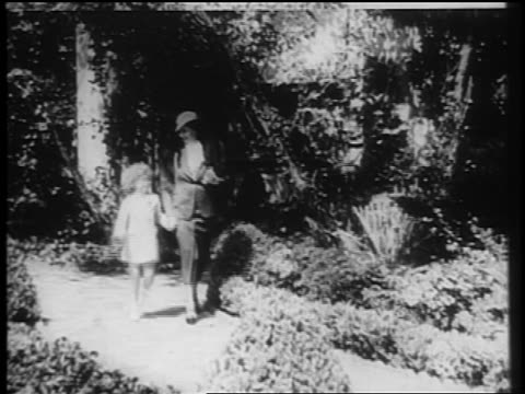 vídeos de stock e filmes b-roll de shirley temple walking skipping outdoors with mother / documentary - shirley temple