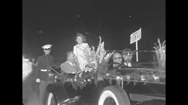 vídeos de stock e filmes b-roll de shirley temple waving with parents gertrude and george temple riding in an open convertible in a nighttime parade - shirley temple