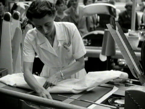 a shirt folding/pressing machine is demonstrated at a laundry exhibition at olympia - exhibition stock videos & royalty-free footage