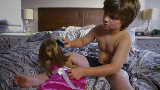 stockvideo's en b-roll-footage met shirtless 8 year old boy combs a dolls hair - borstelen
