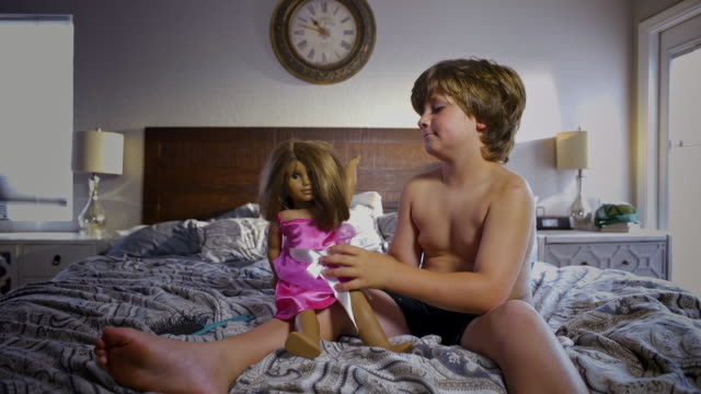 shirtless 8 year old boy plays with a doll - doll stock videos and b-roll footage